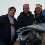 Dallas Parker, left, the Rev. David Wilson and Tim Byington, right, present thermal coats to a camp volunteer at the Oceti Sakawin Camp at Standing Rock. The coats were donated by the Urban Inter-Tribal Center of Texas.